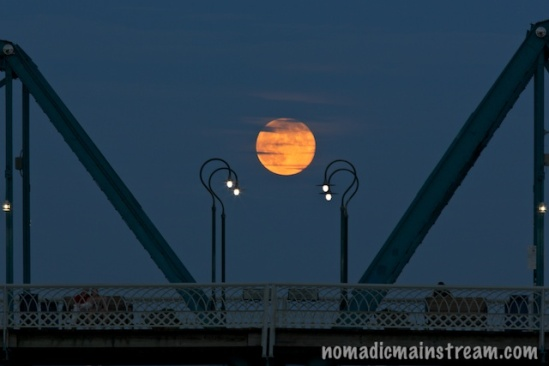 The rising full moon pauses over Walnut Street Bridge