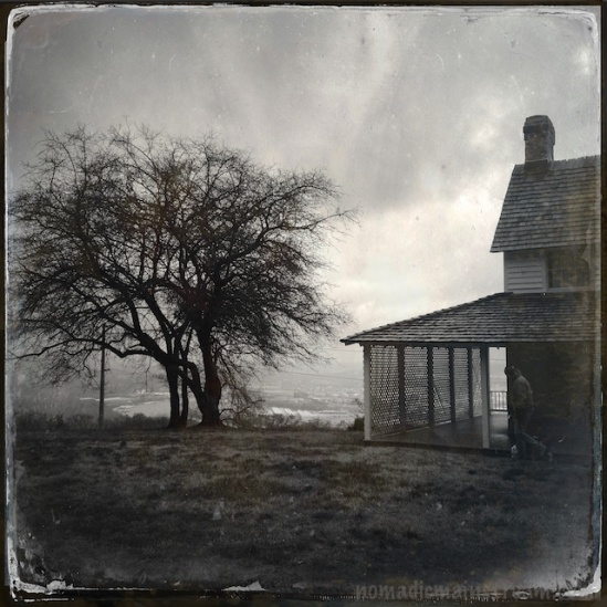 One end of Cravens House with a leafless tree against background clouds
