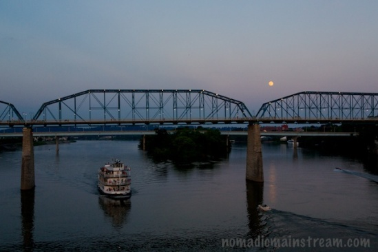 Wide view of moon, bridge, water, and boats