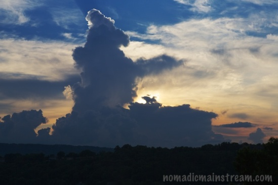 A rising cumulous cloud forms a silhouette in front of the setting sun