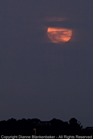 The super moon disappearing behind clouds